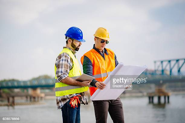 Engineer and construction manager looking at blueprint on site