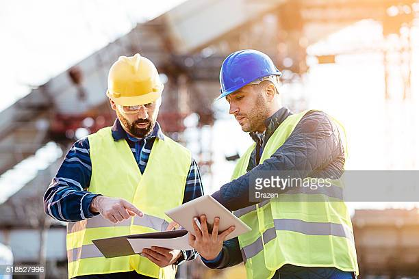 engineer and construction site manager dealing with blueprints and budget - bridge built structure stock pictures, royalty-free photos & images