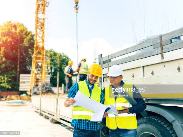 Engineer and construction site manager dealing with blueprints and projects