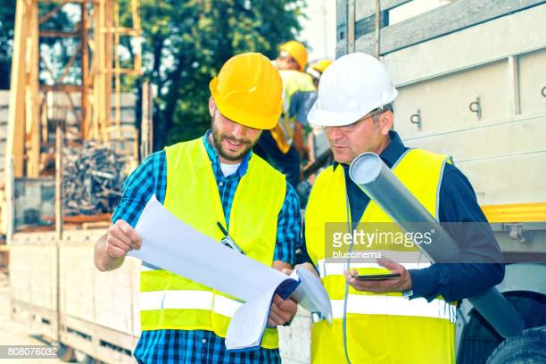 engineer and construction site manager dealing with blueprints and projects - civil engineering stock photos and pictures