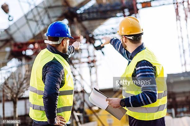 Ingeniero y el sitio de construcción Gerente hablando con la siguiente fase de construcción