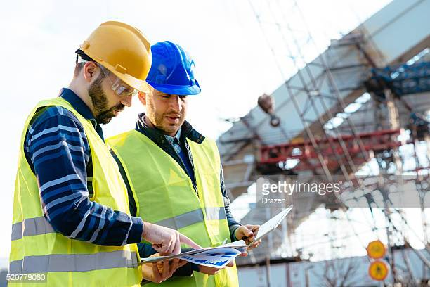 engineer and construction site manager discussing next construction phase - bridge built structure stock pictures, royalty-free photos & images