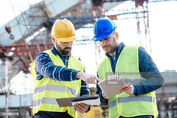 Ingeniero y el sitio de construcción sobre la próxima fase de construcción