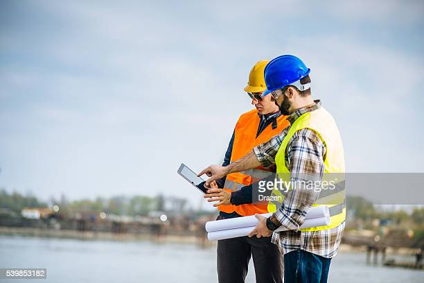 Engineer and construction site manager discussing next construction phase