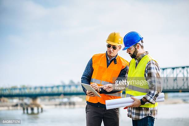 engineer and construction site manager discussing next construction phase - civil engineering stock pictures, royalty-free photos & images