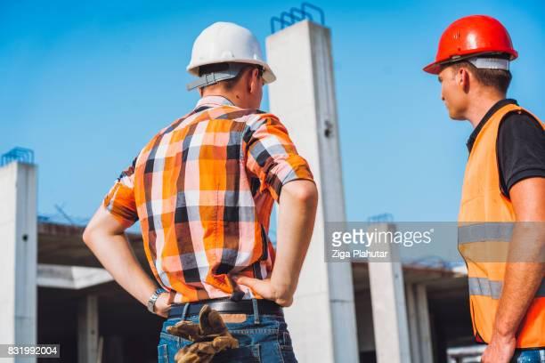 Ingenieur en aannemer met korte bijeenkomst op bouwplaats