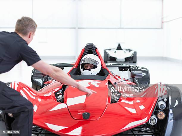 Engineer and racing car driver in supercar in sports car factory