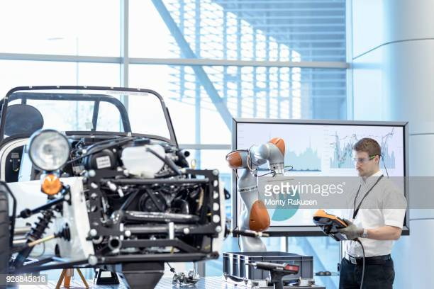 Engineer and robot assembling car in robotics research facility