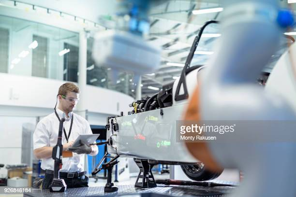 engineer and robot inspecting car in robotics research facility - verkehrswesen stock-fotos und bilder