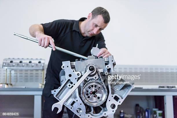 Engineer assembling engine in racing car factory