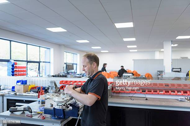 Engineer assembling engine parts in racing car factory