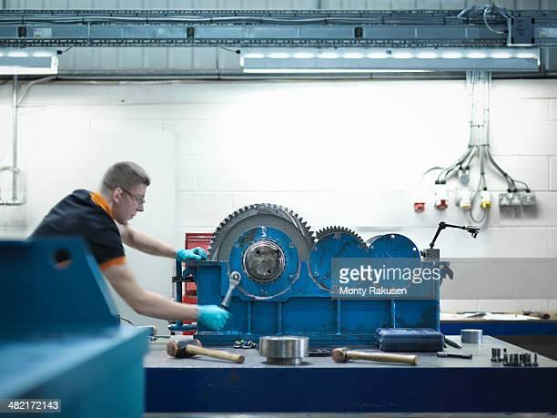 engineer assembling industrial gearbox in engineering factory - monty rakusen stock-fotos und bilder