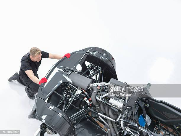 Engineer assembling supercar in sports car factory, high angle view