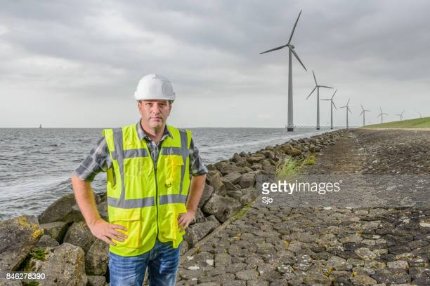 engineer at an offshore wind turbine park during an overcast day - marine engineering stock photos and pictures