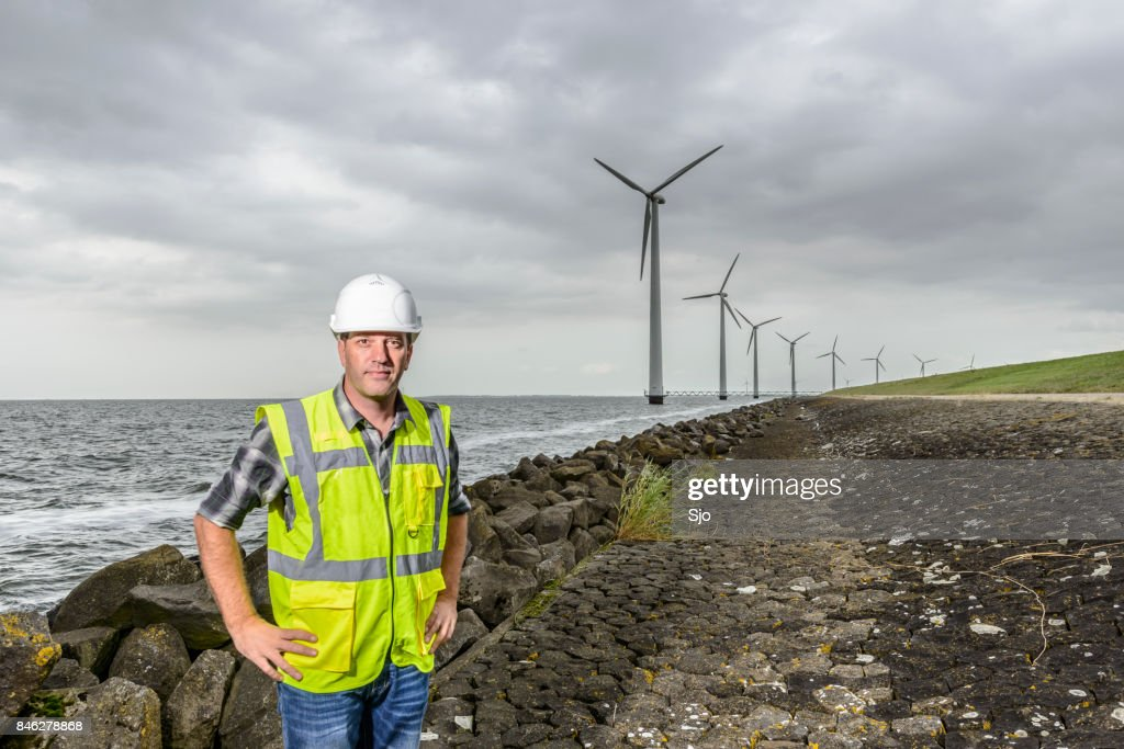Engineer at an offshore wind turbine park during an overcast day : Stock Photo