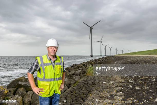 engineer at an offshore wind turbine park during an overcast day - waistcoat stock photos and pictures