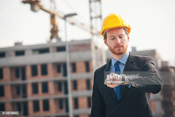 Engineer at construction site checking the watch