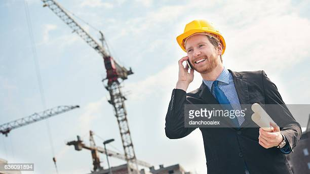 Engineer at construction site talking on the phone