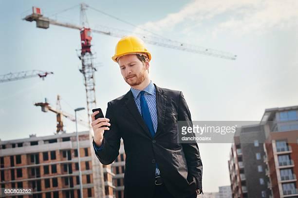 Engenheiro no local de construção usando smartphone