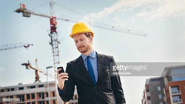 Engineer at construction site using smart phone
