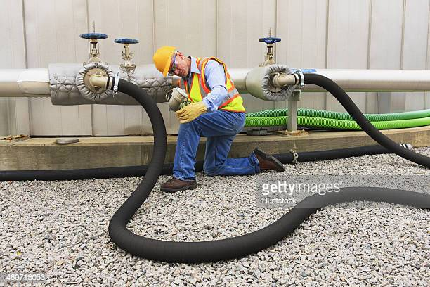 Engineer at electric power plant examining connection hose near water storage tank