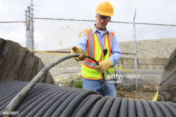 Engineer at electric power plant examining electrical distribution wire at storage area