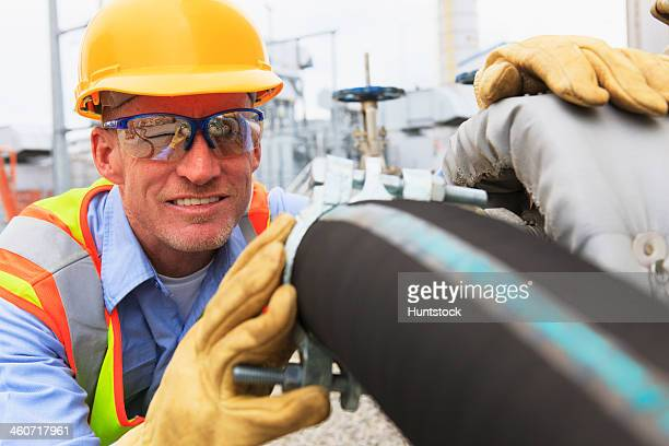 Engineer at electric power plant examining hose for water supply to the water storage tank