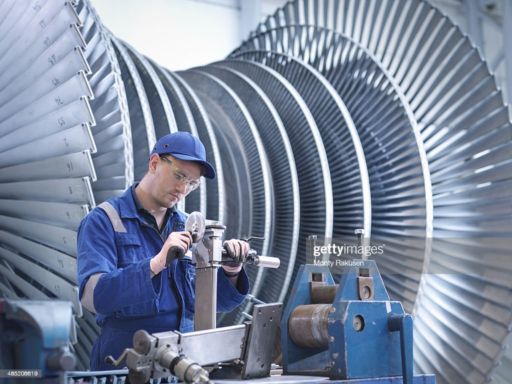 Engineer at workstation in front of steam turbine : Stock Photo