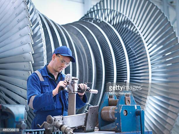 Engineer at workstation in front of steam turbine