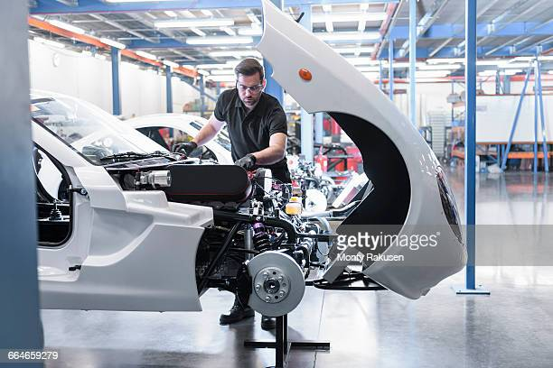 Engineer building car in racing car factory