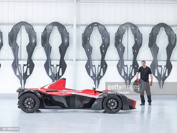 Engineer carrying wheel to supercar in factory with carbon fibre car body shells hanging on wall