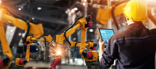 Engineer check and control welding robotics automatic arms machine in intelligent factory automotive industrial with monitoring system software. Digital manufacturing operation. Industry 4.0 1025742788