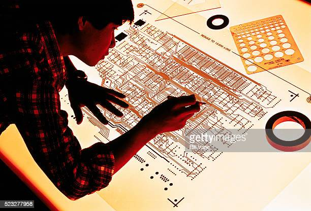 Engineer Checking Blueprint of Integrated Circuits
