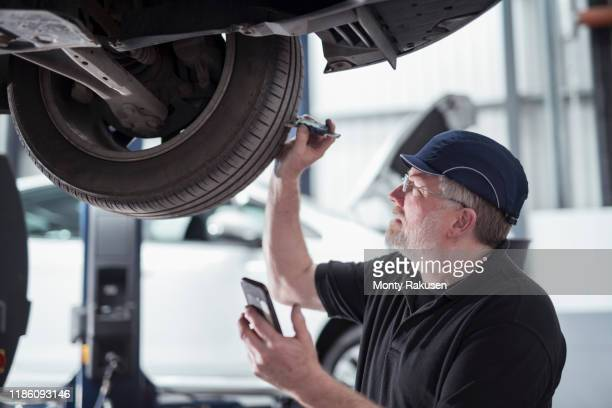 engineer checking car tyre during service in car service centre - examining stock pictures, royalty-free photos & images