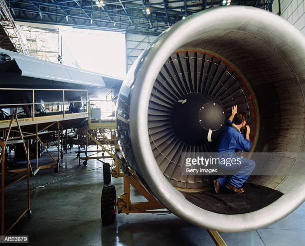 Engineer checking intake blades of airplane