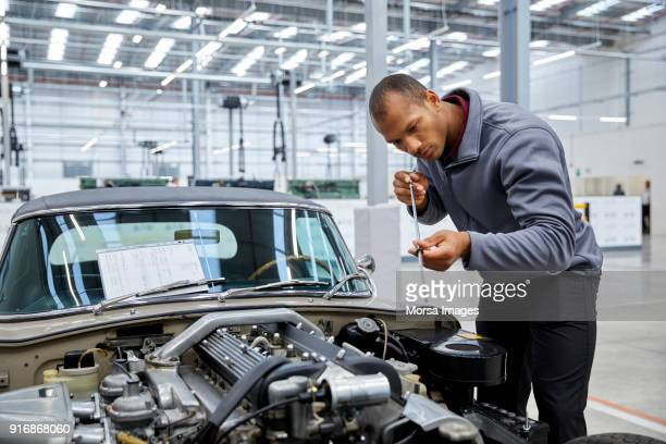 engineer checking motor oil with dipstick by car - oil change stock pictures, royalty-free photos & images