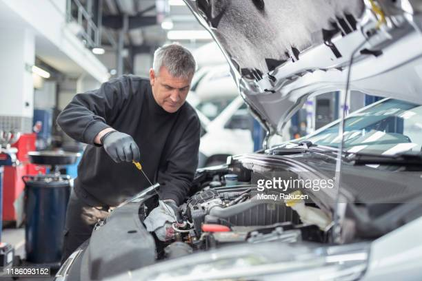 engineer checking oil level in car service centre - repairing stock pictures, royalty-free photos & images