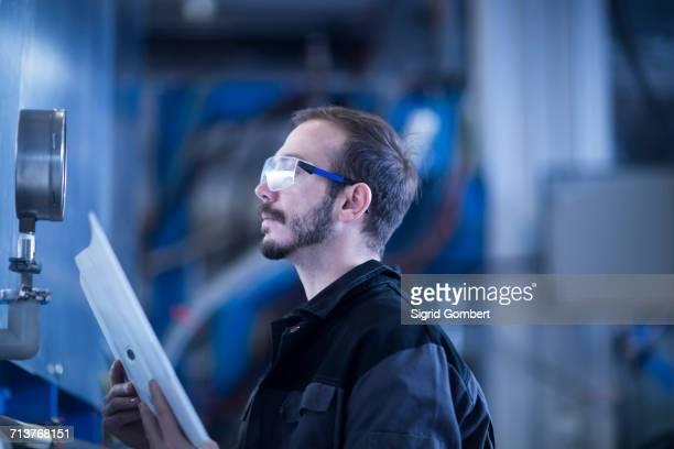 Engineer checking pressure gauge