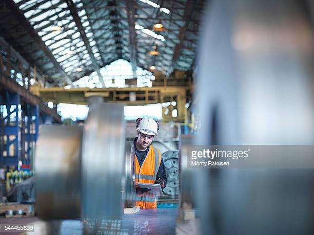 engineer checking steel part in engineering factory - monty rakusen stock-fotos und bilder