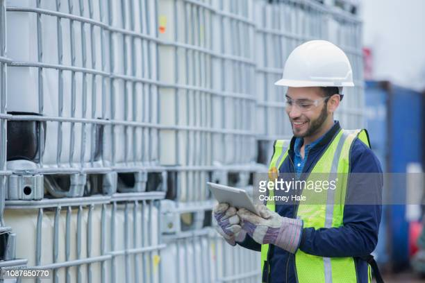engineer checks shipment of chemicals at oil and gas industry pipeline job site - chemistry stock pictures, royalty-free photos & images