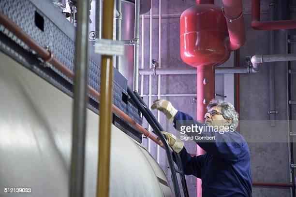 engineer climbing steps in power station - sigrid gombert fotografías e imágenes de stock