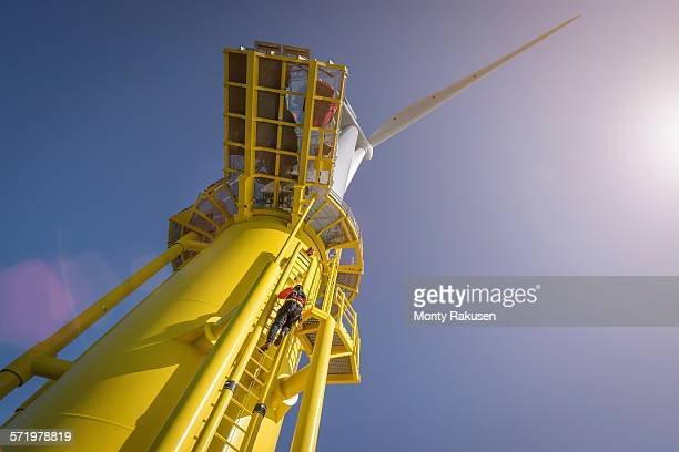 engineer climbing wind turbine from boat at offshore windfarm, low angle view - marine engineering stock pictures, royalty-free photos & images