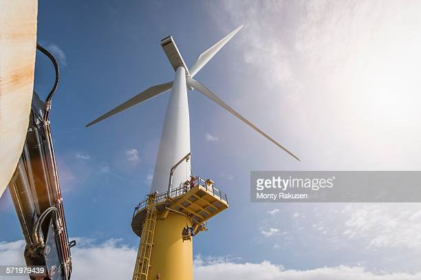 engineer climbing wind turbine from boat at offshore windfarm - marine engineering stock pictures, royalty-free photos & images