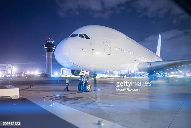 Engineer communicating with pilot of A380 aircraft on runway at night