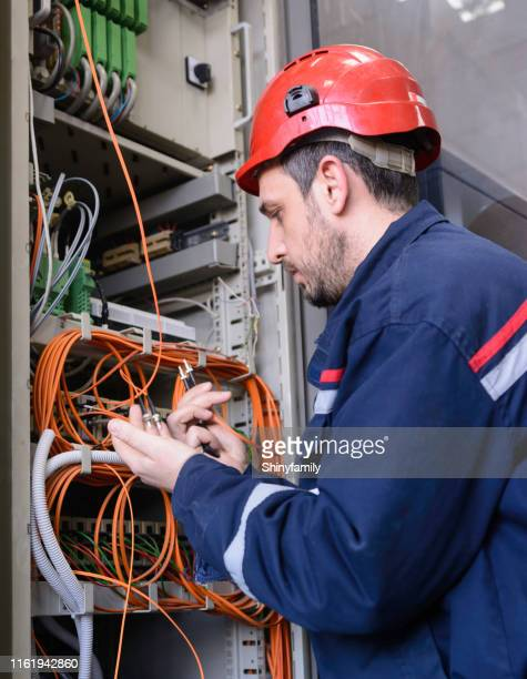 engineer connecting fiber optic cable to the switch - communication occupation stock pictures, royalty-free photos & images