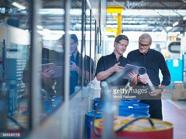engineer designers discussing plans on digital tablet in factory - portable information device stock-fotos und bilder