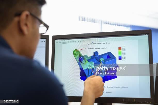 engineer designing gearboxes using computer aided design (cad) software in gearbox factory - rechnerunterstütztes konstruieren stock-fotos und bilder