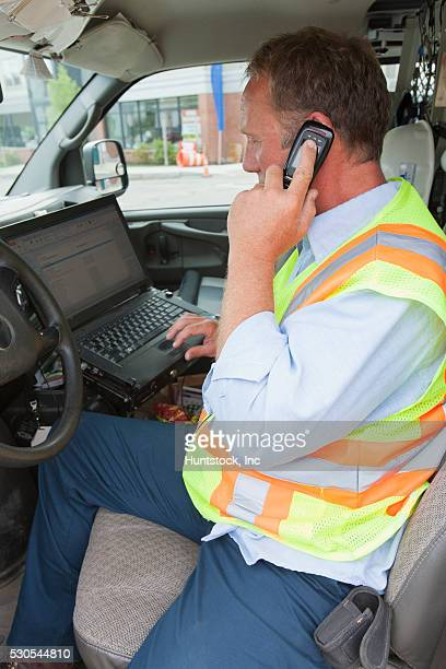 Engineer entering data about public water samples on computer in truck