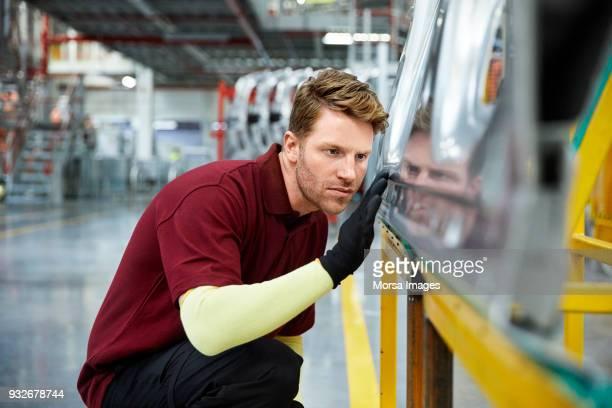 Engineer examining car part in industry