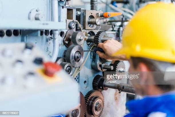 Engineer fixing cog wheels, gears and machine teeth
